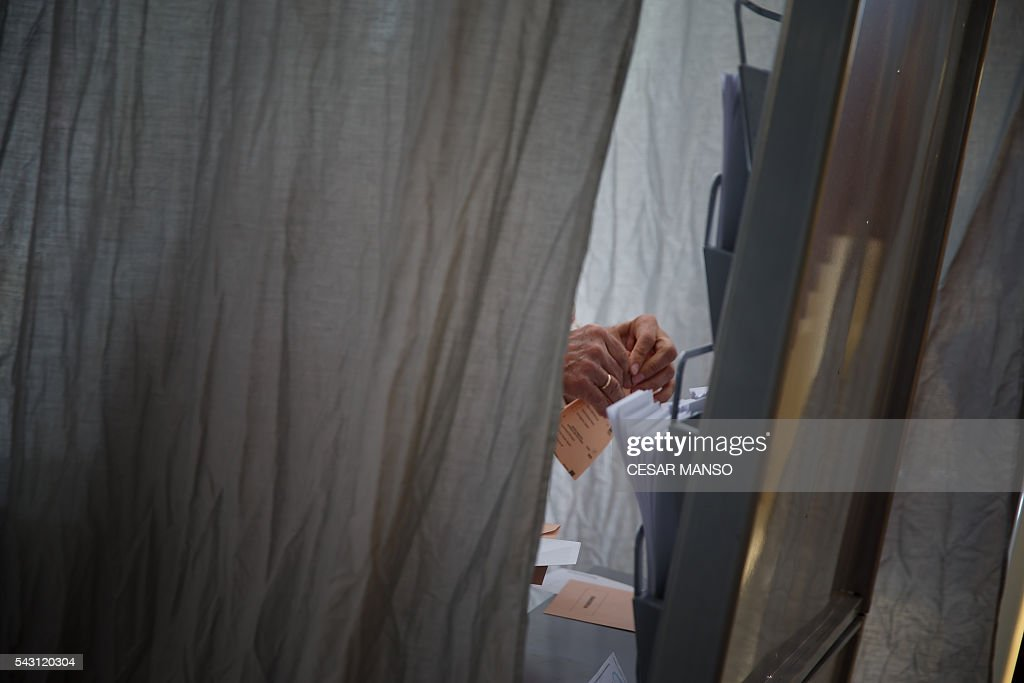 A woman gathers election material to vote in Spains general election at the Bernadette college polling station in Moncloa-Aravaca, Madrid, on June 26, 2016. Spain votes today, six months after an inconclusive election which saw parties unable to agree on a coalition government. MANSO