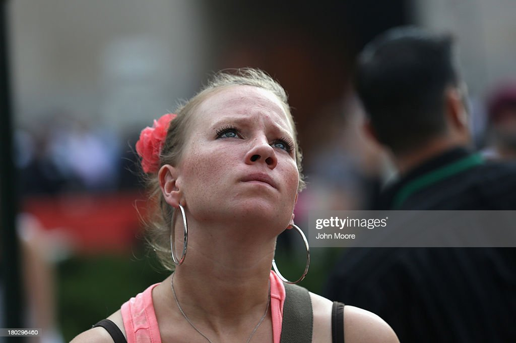 A woman gazes at the One World Trade Center as church bells toll for 9/11 victims on September 11, 2013 in New York City. The nation is commemorating the anniversary of the 2001 attacks which resulted in the deaths of nearly 3,000 people after two hijacked planes crashed into the World Trade Center, one into the Pentagon in Arlington, Virginia and one crash landed in Shanksville, Pennsylvania. Following the attacks in New York, the former location of the Twin Towers has been turned into the National September 11 Memorial & Museum.