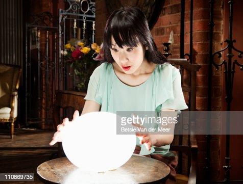 Woman gazes into crystal ball. : Bildbanksbilder
