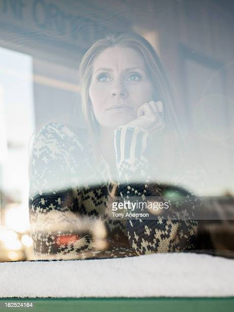 Woman gazing out window of cafe