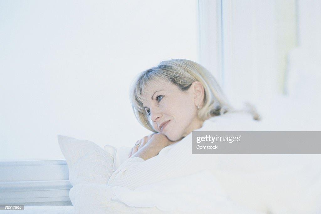 Woman gazing out window : Stock Photo