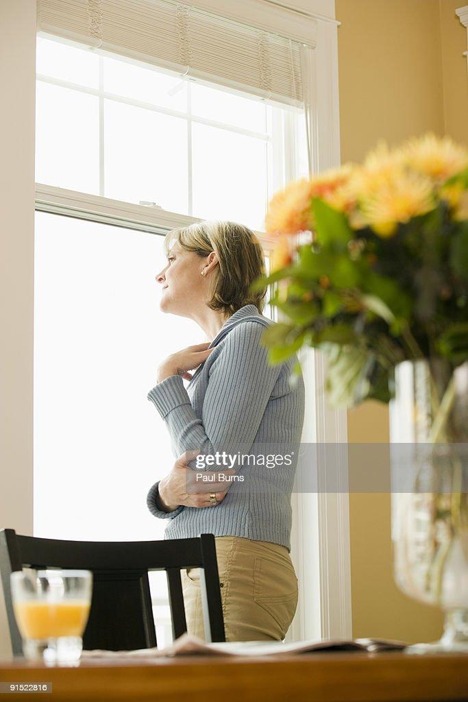 Woman gazing outside by the window