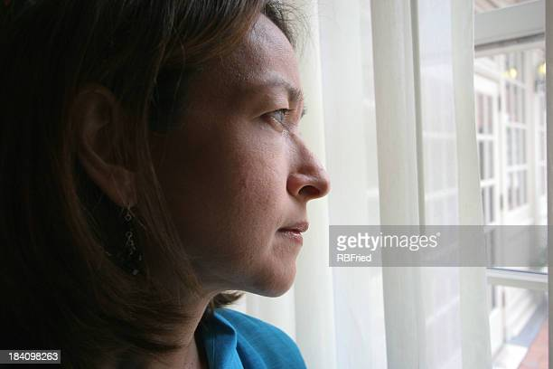 Woman gazing pensively out a window