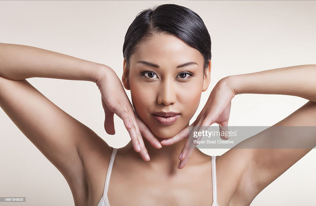 Woman gently touching the edges of her cheeks : Stock Photo