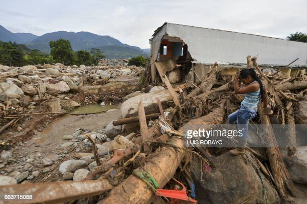TOPSHOT A woman gestures amid the damage caused by mudslides following heavy rains in Mocoa Putumayo department southern Colombia on April 2 2017 The...