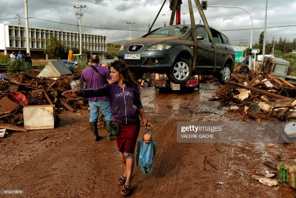 TOPSHOT - A woman gestures as a car is removed from the road in the town of Mandra, northwest of Athens, on November 15, 2017, after heavy overnight rainfall in the area caused damage and left seven people dead. At least seven people died on November 15 and more were missing after a strong overnight downpour flooded three towns in Greece, officials said. The flooding struck the towns of Mandra, Nea Peramos and Megara, a semi-rural area west of Athens where many factories and warehouses are based. GACHE
