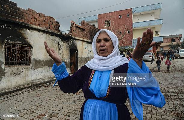A woman gestures as she complains about damage done to her house during fighting between government troops and separatist Kurdistan Workers' Party...