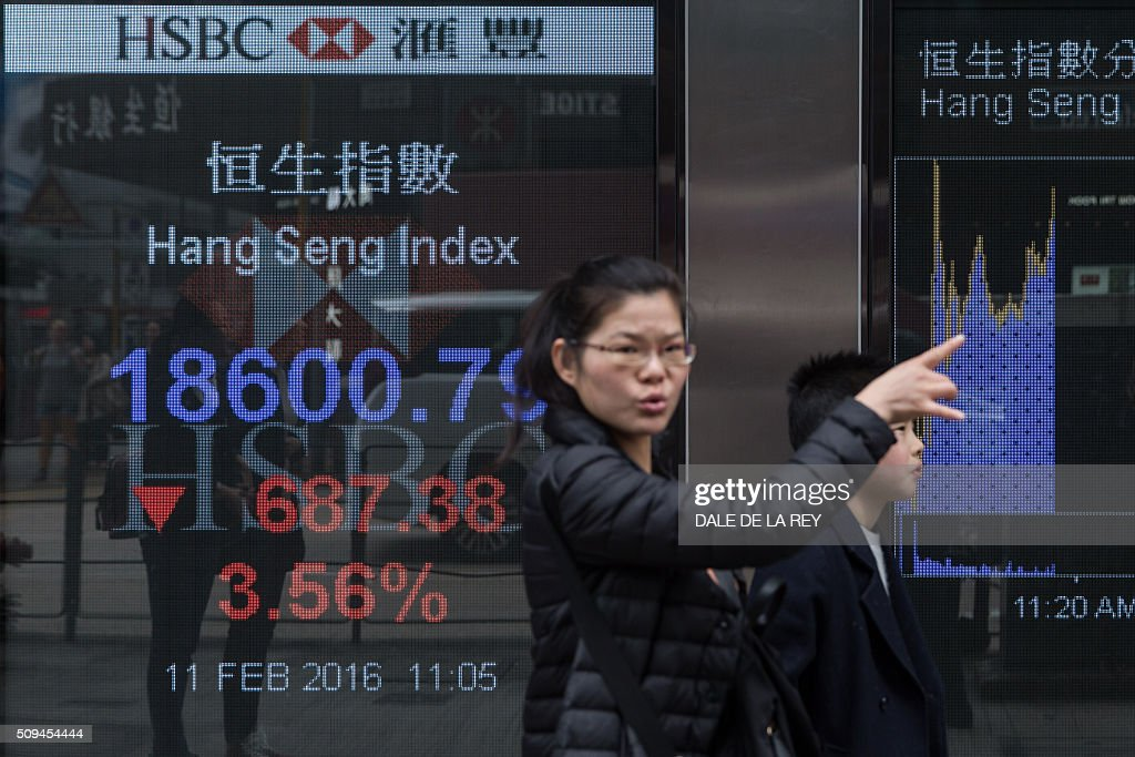 A woman gestures as she walks past a display showing the Hang Sang index outside a bank on the first day of trading of the Lunar New Year in Hong Kong on February 11, 2016. Hong Kong stocks plunged more than four percent to a more than three-year low on February 11, leading another sell-off across Asian markets and extending a global rout fanned by worries over the world economy. AFP PHOTO / DALE DE LA REY / AFP / DALE de la REY