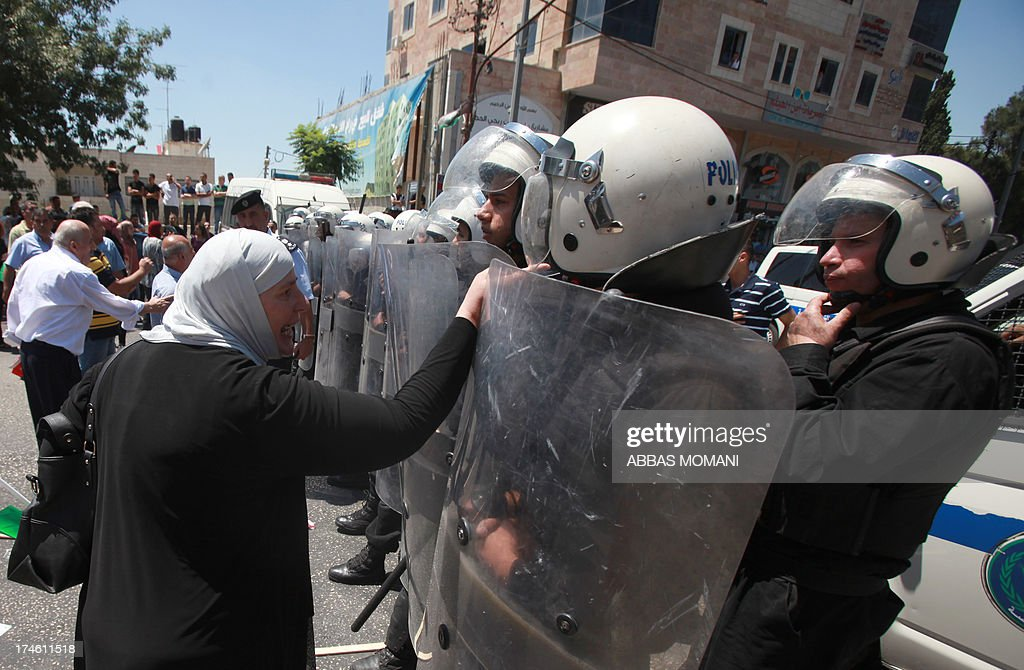 A woman gestures at a Palestinian riot policeman as protesters demonstrating against the upcoming negotiations between Palestinian leaders and Israel, march towards the headquarters of Palestinian president Mahmud Abbas, in the West Bank city of Ramallah on July 28, 2013. A Palestinian official told AFP that the US-brokered renewal of peace talks, stalled since September 2010, would open in Washington this coming week.