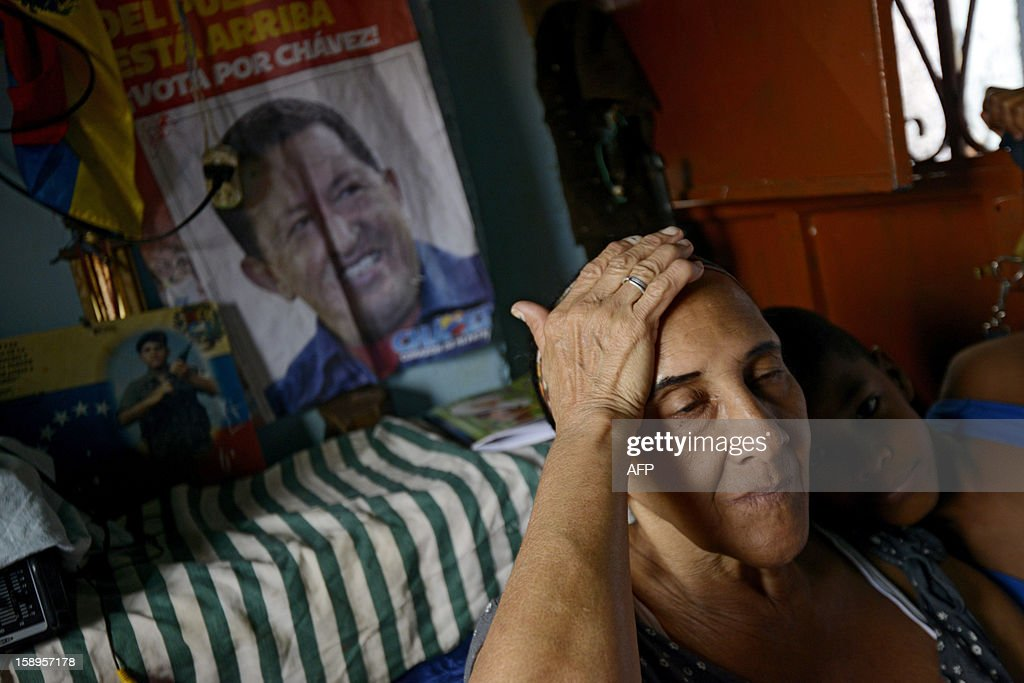 A woman gestures at her home next to a poster of Venezuelan President Hugo Chavez in the popular sector of San Agustin, in Caracas on January 4, 2013. Hugo Chavez's top aides have gone on the offensive, accusing the opposition and media of waging a 'psychological war,' as Venezuela's cancer-stricken president battles a serious lung infection. The closing of ranks followed a high-level gathering of top Venezuelan officials in Havana with Chavez, amid growing demands to know whether he will be fit on January 10 to take the oath of office for another six-year-term. AFP PHOTO/Leo Ramirez