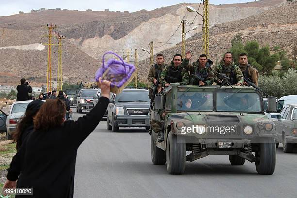 A woman gestures to a convoy of the Lebanese army in the village of Labweh in the Bekaa Valley on December 1 as Lebanese soldiers and policemen...