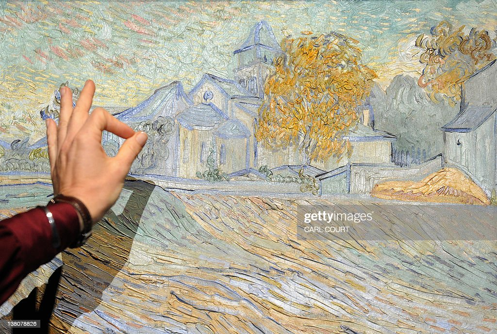 A woman gestures towards an 1889 painting by Dutch painter Vincent Van Gogh entitled 'Vue de l'Asile et de la Chapelle de Saint-Remy' during a press preview prior to the 'Impressionist and Modern Art Sale' at Christie's auction house in central London on February 2, 2012. From the collection of late actress Elizabeth Taylor, it will come under the hammer on February 7, 2012 and is expected to fetch between 5 - 7million British pounds (7.6 - 11 million US dollars, 5.7 - 7.9 million euros).