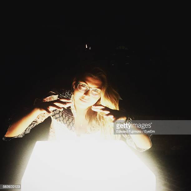 Woman Gesturing Over Glowing Book