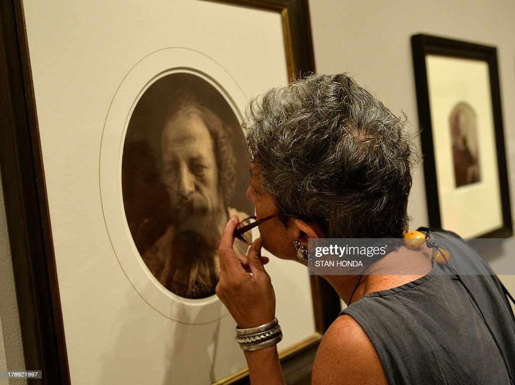 A woman gets a close look at Alfred, Lord Tennyson, July 4, 1866' a photograph on display in the exhibition 'Julia Margaret Cameron' featuring work by the great British photographer Julia Margaret Cameron (1815-1879) August 19, 2013 at The Metropolitan Museum of Art in New York. Lord Tennyson was a neighbor of Cameron on the Isle of Wight in Britain.The exhibition is open from August 19, 2013 to January 5, 2014. AFP PHOTO/Stan HONDA