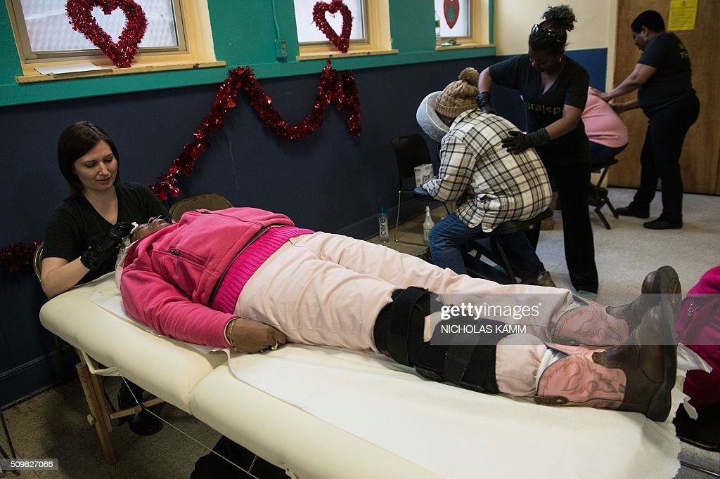 A woman gets a facial skin treatment as others get a massage during a Spa Day for homeless and at-risk women organized by ThriveDC, an organization fighting homelessness, in Washington, DC, on February 12, 2016. Recent research published in the American Journal of American Health finds that unstably-housed women experience dramatically higher incidence of physical, sexual and emotional violence. / AFP / Nicholas Kamm