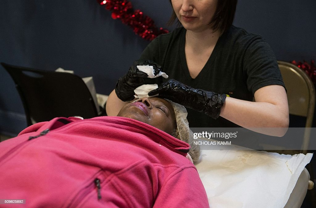 A woman gets a facial skin treatment during a Spa Day for homeless and at-risk women organized by ThriveDC, an organization fighting homelessness, in Washington, DC, on February 12, 2016. Recent research published in the American Journal of American Health finds that unstably-housed women experience dramatically higher incidence of physical, sexual and emotional violence. / AFP / Nicholas Kamm