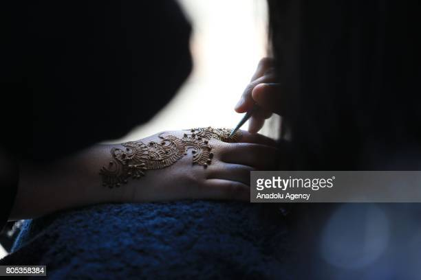 A woman gets a henna tattoo from a stand holder at the Eid festival at the Old Trafford stadium in Manchester United Kingdom on July 01 2017
