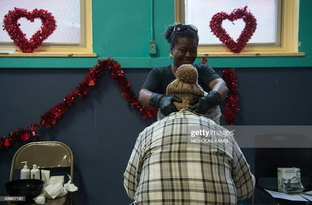 A woman gets a massage during a Spa Day for homeless and at-risk women organized by ThriveDC, an organization fighting homelessness, in Washington, DC, on February 12, 2016. Recent research published in the American Journal of American Health finds that unstably-housed women experience dramatically higher incidence of physical, sexual and emotional violence. / AFP / Nicholas Kamm
