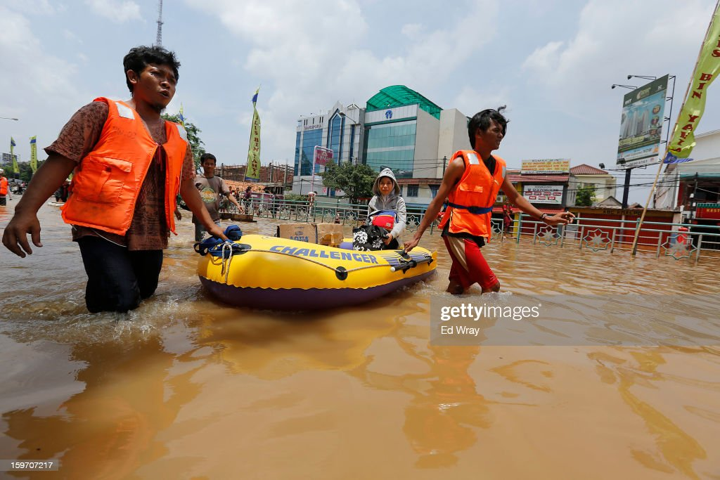 A woman gets a ride across a flooded road in a dingy on January 19, 2013 in Jakarta, Indonesia. Floodwaters receded today after three days of heavy flooding which left thousands of people's homes underwater. According to Indonesian police the death toll has reached 15.