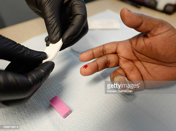 A woman gets an istant HIV/AIDS test inside a moblile clinic of John Wesley Community Health Institute during a health fair sponsored by World...