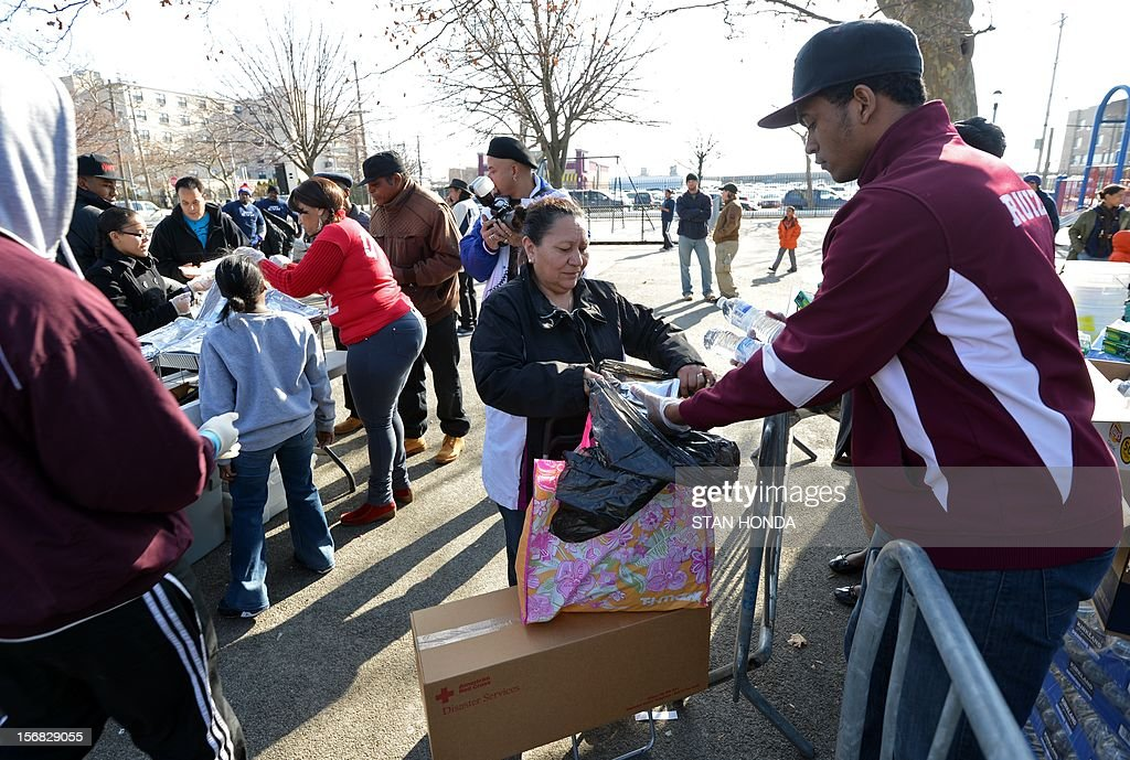 A woman (C) gets donations of supplies at a distribution point on Beach Channel Drive in the Rockaways section of Queens on November 22, 2012 in New York as the city recovers from the effects of superstorm Sandy. Volunteers (L, rear) served Thanksgiving dinner to area residents. AFP PHOTO/Stan HONDA