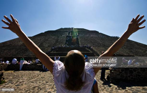 A woman gets energy from the sun in front of the Pyramid of the Sun in Teotihuacan Mexico during the celebrations for the Spring Equinox on March 21...