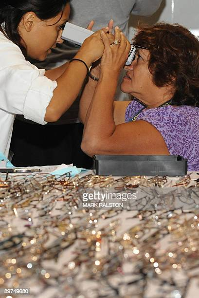 A woman gets her eyes checked as volunteer medical staff offer free medical vision and dental services to those without health insurance and in need...