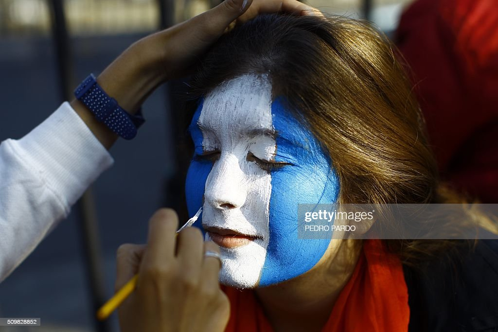 A woman gets her face painted before Pope Francis' arrival in Mexico City on February 12, 2016. Pope Francis will arrive in Mexico on Friday, where he will visit until February 17. AFP PHOTO/ Pedro PARDO / AFP / Pedro PARDO