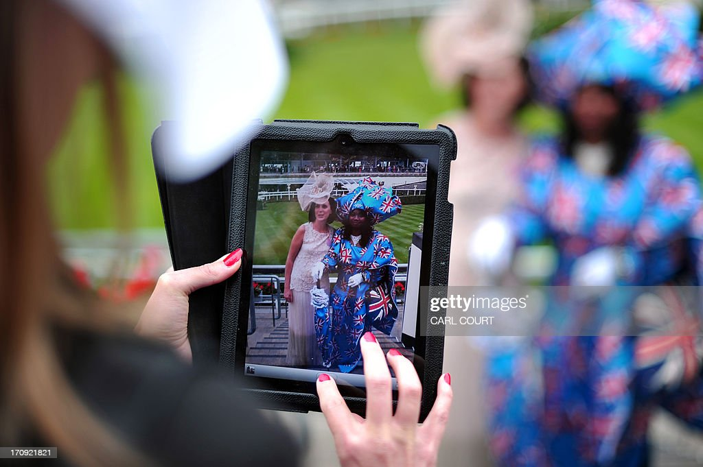 A woman gets her picture taken as she poses with another in a fancy outfit on the third day of Royal Ascot, in Berkshire, west of London, on June 20, 2013. The five-day meeting is one of the highlights of the horse racing calendar. Horse racing has been held at the famous Berkshire course since 1711 and tradition is a hallmark of the meeting. Top hats and tails remain compulsory in parts of the course while a daily procession of horse-drawn carriages brings the Queen to the course.