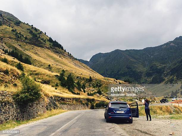 Woman gets out of the car and takes photos of the surrounding mountains Carpathians Romania