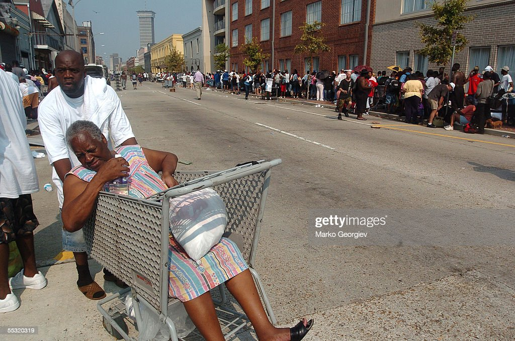 A woman gets pushed in shopping cart while displaced flood survivors wait in line to enter buses during the evacuation of the Convention center on...