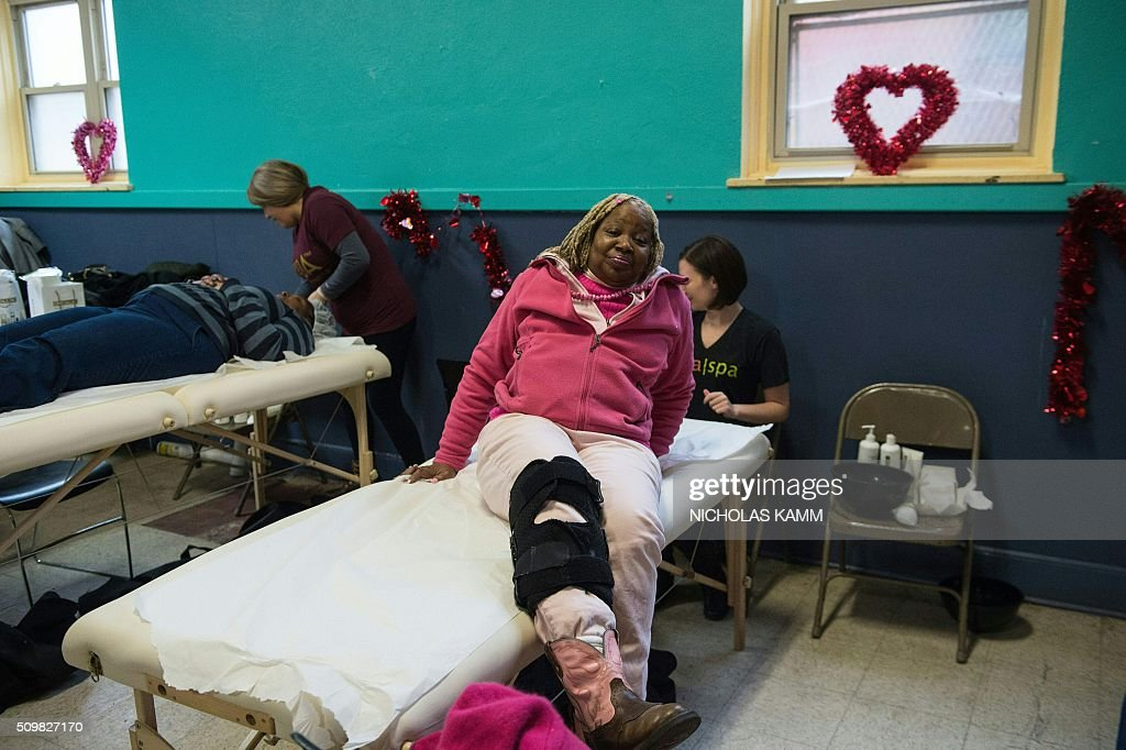 A woman gets up after a facial skin treatment as others get a massage during a Spa Day for homeless and at-risk women organized by ThriveDC, an organization fighting homelessness, in Washington, DC, on February 12, 2016. Recent research published in the American Journal of American Health finds that unstably-housed women experience dramatically higher incidence of physical, sexual and emotional violence. / AFP / Nicholas Kamm
