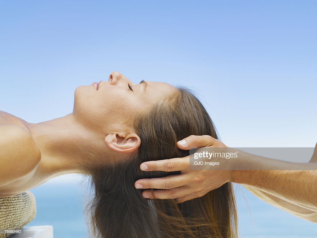 Woman getting a head massage from a masseur : Stock Photo