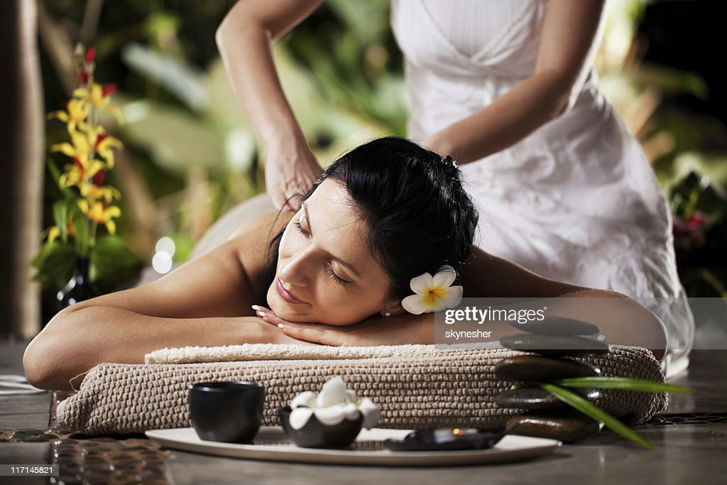 Woman getting a massage at tropical spa