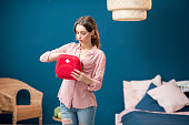 Woman getting a pills from first aid kit standing indoors in the blue living room at home
