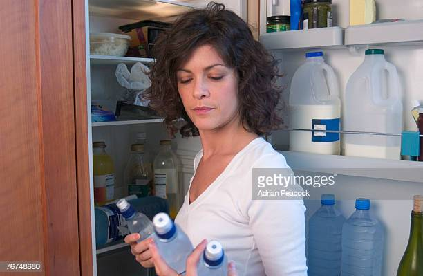 Woman getting bottled water from refrigerator