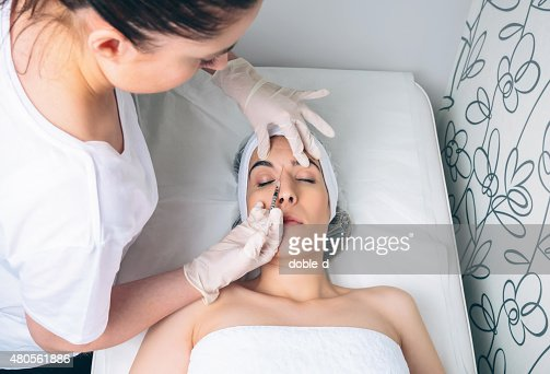 Woman getting cosmetic injection in her face on clinical center : Stock Photo