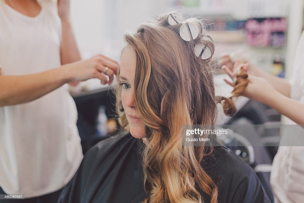 Woman getting curls from hairdressers