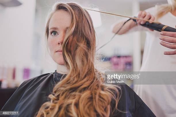 Woman getting curls in coiffeur studio