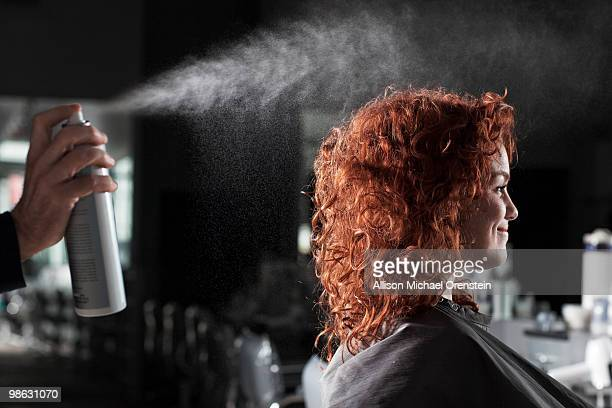 woman getting hair sprayed at salon