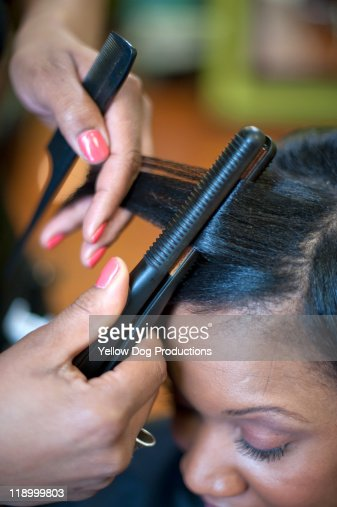 Woman getting hair straightened in salon
