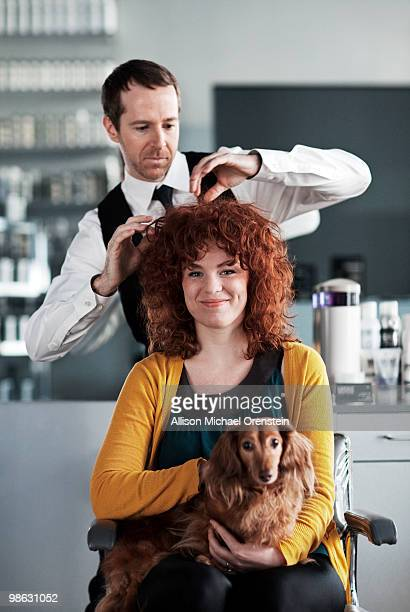 Woman getting haircut with dog on her lap