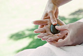 Woman getting hand massage with hot stone