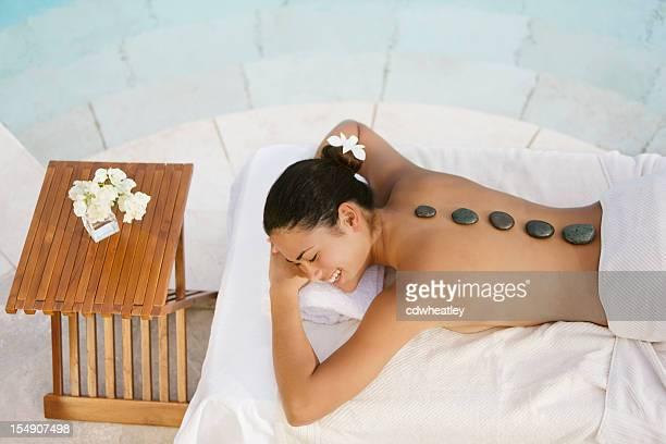 Mulher a receber uma Massagem de pedras quentes no spa do resort de luxo