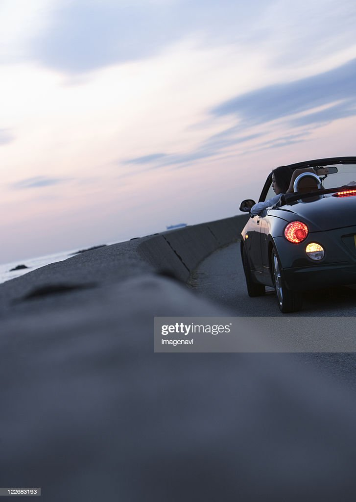 A woman getting in a convertible