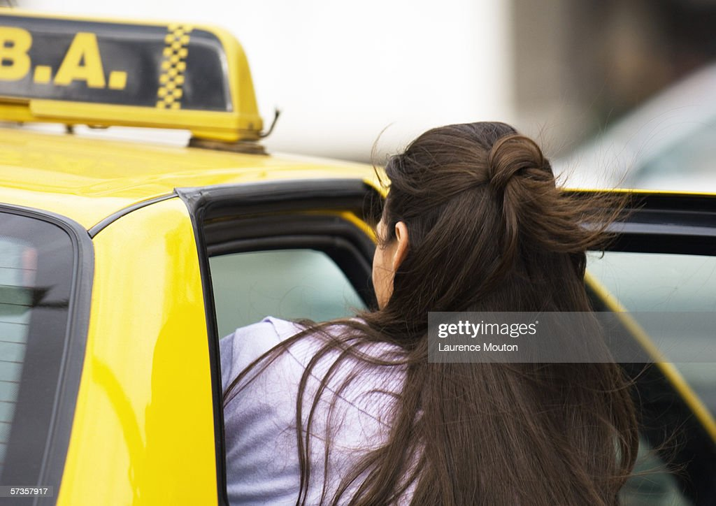 Woman getting in taxi : Stock Photo