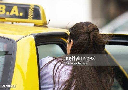 Woman getting in taxi : Stock Photo