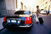Woman getting into car with luggage