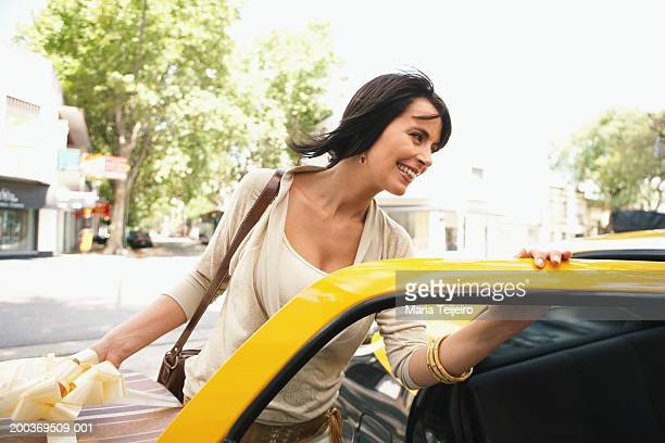 Woman getting into taxi holding hat box, smiling