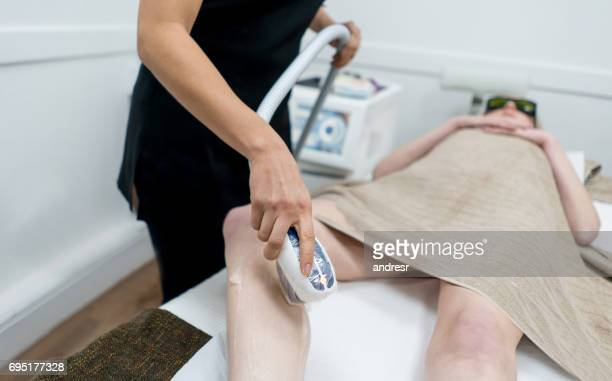 Woman getting laser hair removal on her legs at the spa